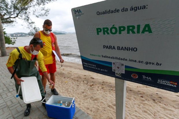 #Pracegover Na foto, um placa indicando que a praia é prória para banho e duas pessoas fazendo a coleta de materiais
