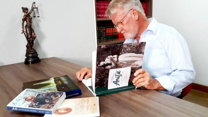 #Pracegover Foto: na imagem há um homem, uma estante, uma imagem, livros e uma mesa