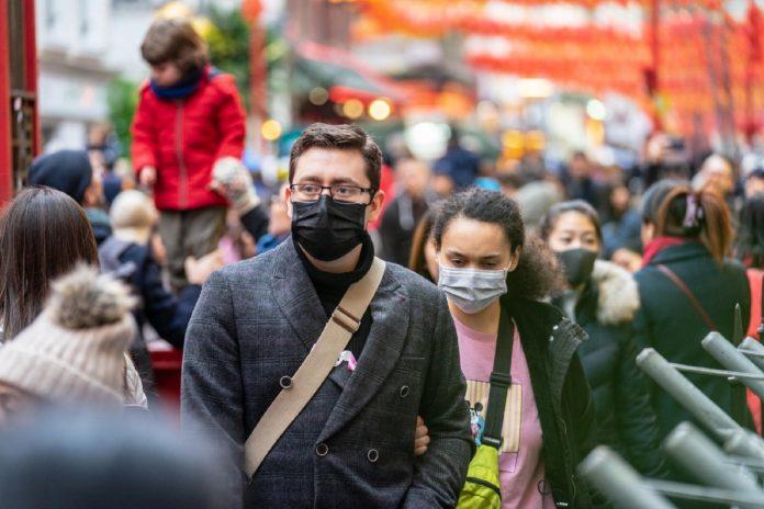 #Pracegover Foto: na imagem há pessoas de máscaras caminhando na rua
