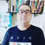 #Pracegover Foto: na imagem há um homem de óculos e camiseta preta. Há também livros