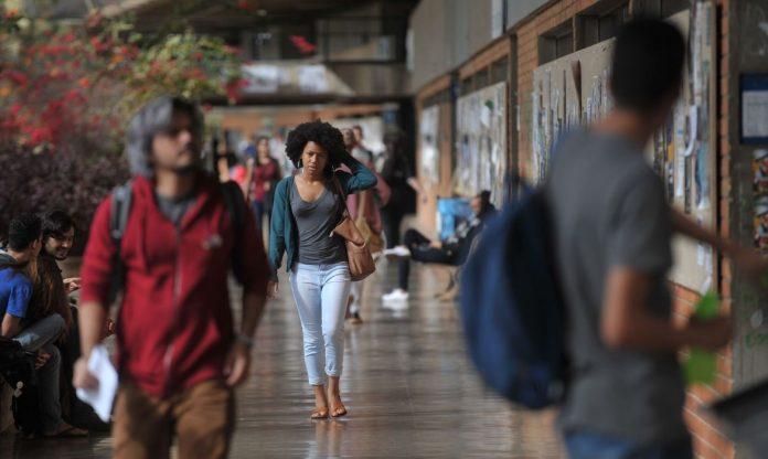 #Pracegover Foto: na imagem há algumas pessoas caminhando em uma universidade