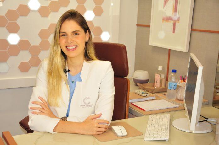 #Pracegover Foto: na imagem há uma mulher sorridente, um teclado, computador e uma garrafa de água