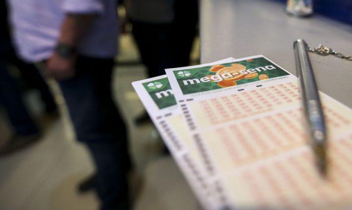 #Pracegover Foto: na imagem há voantes da Mega-Sena e pessoas em uma fila