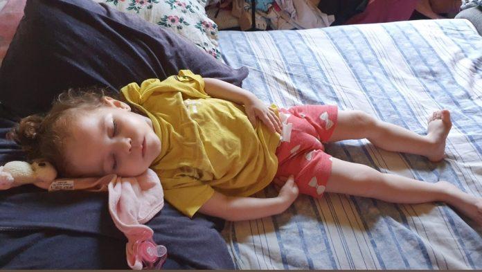 #Pracegover Foto: na imagem há uma criança dormindo em uma cama