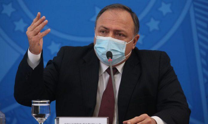 #Pracegover Foto: na imagem há um homem de terno e máscara falando ao microfone