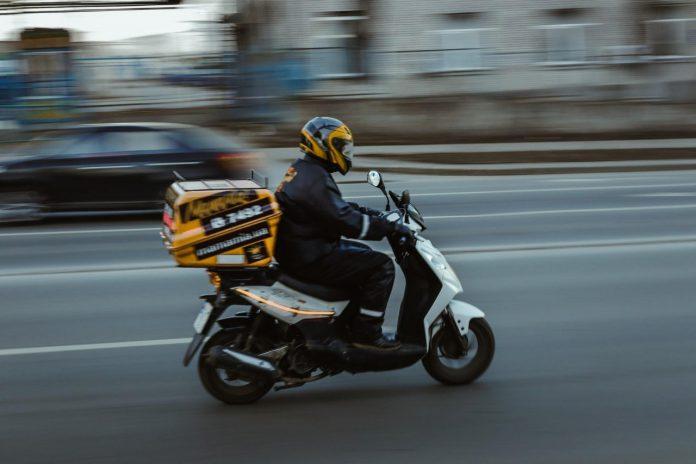 #Pracegover Foto: na imagem há uma pessoa andando de moto com encomenda
