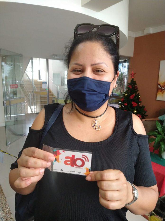 #Pracegover Foto: na imagem há uma mulher de máscara segurando um chip telefônico