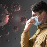#Pracegover Na foto, uma montagem de cenas com homem usando máscara e a sua frente células de Covid-19