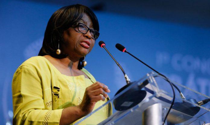 #Pracegover Foto: na imagem há uma mulher de óculos, dois microfones