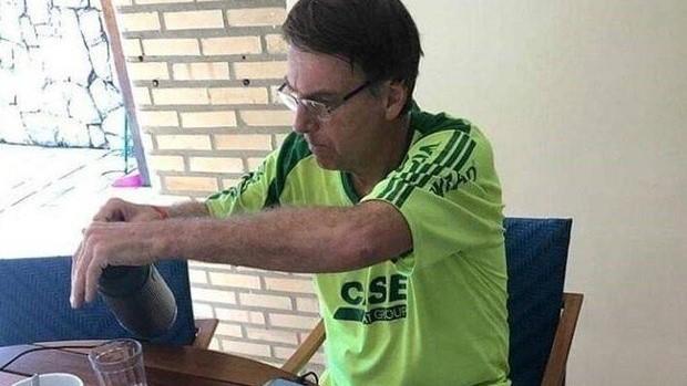 #Pracegover Na foto, Bolsonaro aparece tomando café