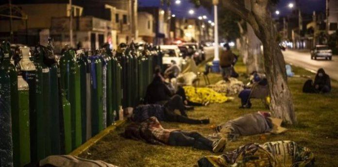 #Pracegover Na foto, a imagem de pessoas dormindo na grama ao lado de cilindro de oxigênio