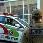 #Pracegover Na foto, um policial de costas em frente a uma viatura