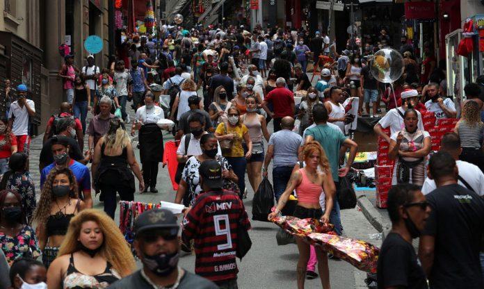 #Pracegover Foto: na imagem há muitas pessoas em um comércio de rua. Algumas com máscaras e outras sem