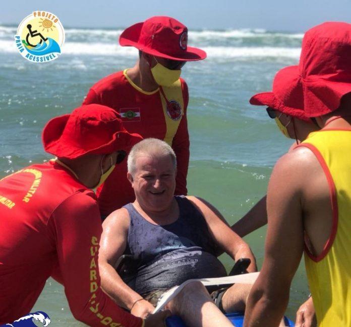 #Pracegover Na foto, Bombeiros seguram uma cadeira anfíbia enquanto um banhista tomar um banho no mar
