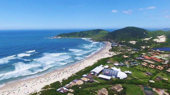 #Pracegover Foto: na imagem há o mar, faixa de areia, casas e uma área verde