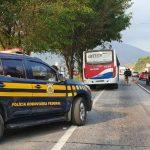 #Pracegover Foto: na imagem há uma viatura da PRF, ônibus, veículos e pessoas