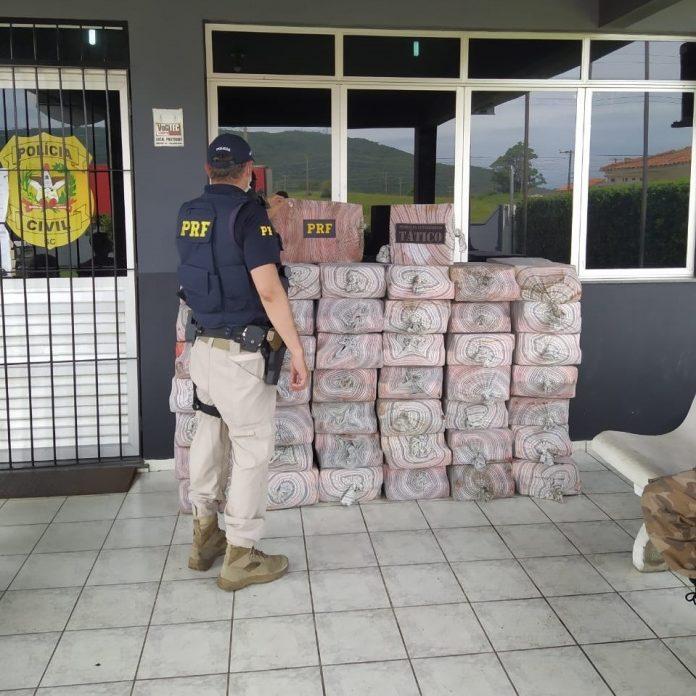 #Pracegover Na foto, um agente da PRF em frente às drogas apreendidas