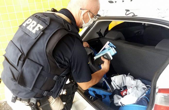 #Pracegover Na foto, a imagem de um policial retirando celulares enrolado em roupas