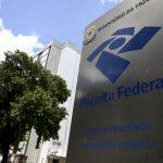 #Pracegover Foto: na imagem há uma placa da Receita Federal, árvore e um edifício