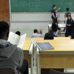 #Pracegover Foto: na imagem há alunos, carteiras, folhas e quadro