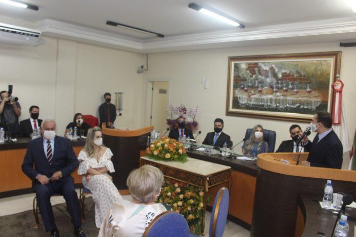 #Pracegover Foto: na imagem há pessoas, cadeiras, mesas púpitos, flores e microfones