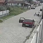 #Pracegover Foto: na imagem há uma rua, carros, moto, casas e um terreno baldio