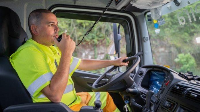 #Pracegover Na foto, um motorista com um microfone na mão falando em um rádio comunicador