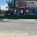 #Pracegoover Foto: na imagem há uma casa, rua e alguns matos pela calçada