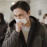 #Pracegover Na foto, um homem usa usa máscara e tapa boca para tossir