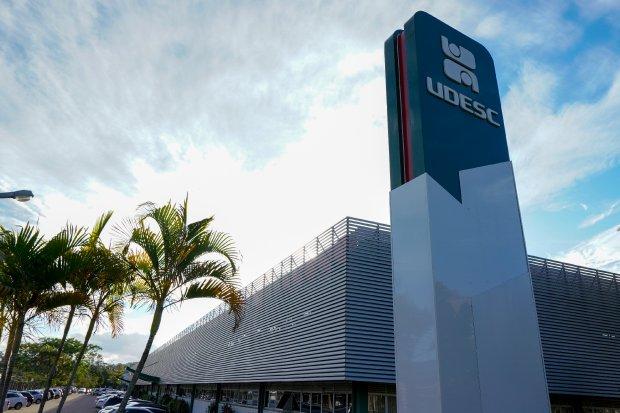 #Pracegover Foto: na imagem há um prédio e uma palmeira