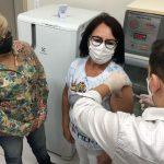 #Pracegover Foto: na imagem há duas mulher e um homem. O homem é médico e aplica a vacina em uma das mulheres