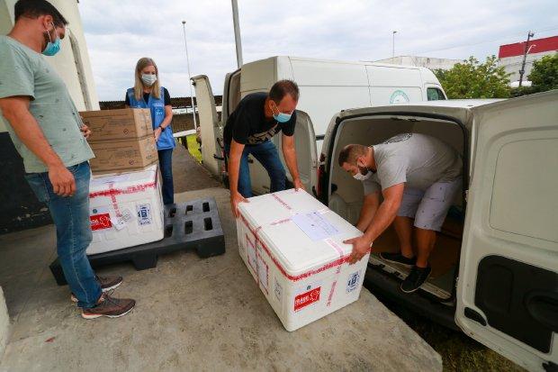 #Pracegover Foto: na imagem há homens, caixas de vacinas e veículos