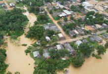 #Pracegover Foto: na imagem há muitas residências que estão embaixo de água, árvores e ruas