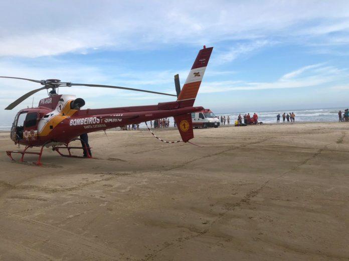 #Pracegover Foto: na imagem há uma aeronave, ambulância, areia, mar e pessoas