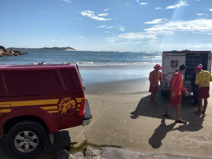 #Pracegover Foto: na imagem há um veículo do Corpo de Bombeiros, um veículo do IML, três homens, o mar e a faixa de areia