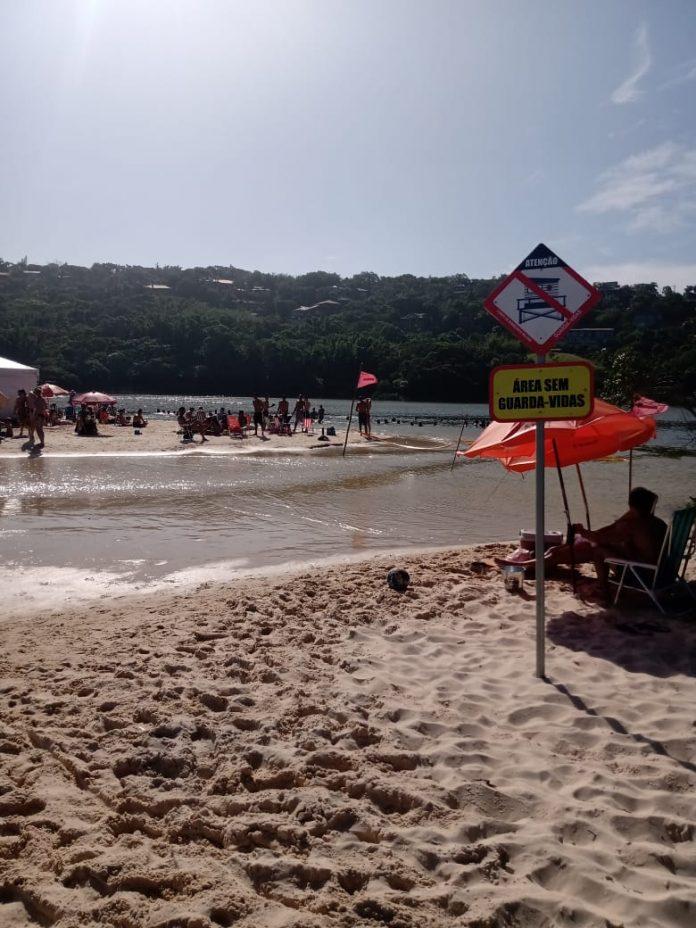 #Pracegover Foto: na imagem há areia, uma lagoa, guarda-sol, sinalização e pessoas na água