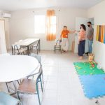 #Pracegover Foto: na imagem há três pessoas, cadeiras, mesa, tapetes, armário e brinquedos