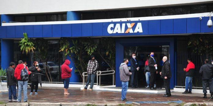 #Pracegover Na foto, pessoas em fila em frente agência bancária