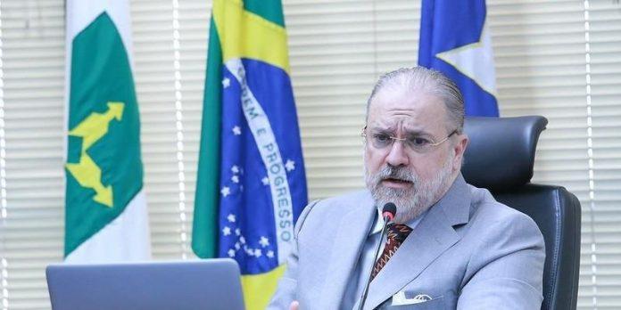 #Pracegover Foto: na imagem há um homem, notebook e três bandeiras