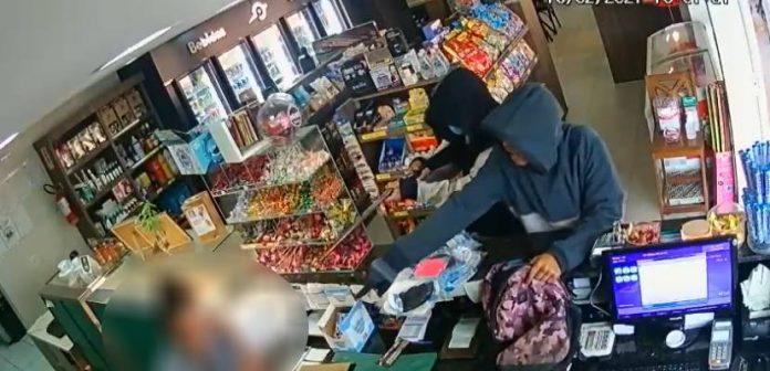 #Pracegover Na foto, funcionária do posto de combustível entregando o dinheiro para os bandidos