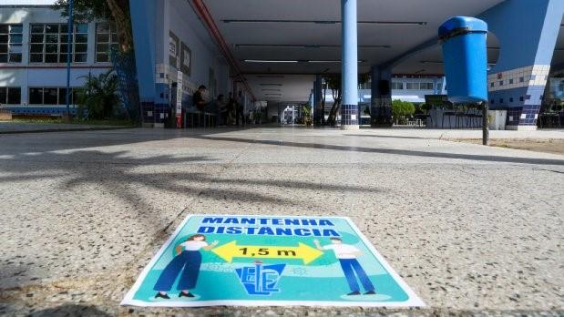 #Pracegover Na foto, a entrada de uma escola e um tapete orientando distanciamento