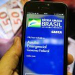 #Pracegover Foto: na imagem há uma mão, um celular e cédulas em reais