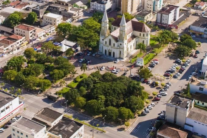 #Pracegover Foto: na imagem há árvores, uma igreja, ruas e outras edificações
