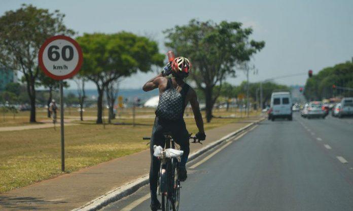 #pracegover Na foto, um ciclista em uma estrada em um dia ensolarado