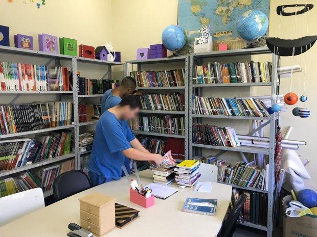 #Pracegover Foto: na imagem há livros, mesa, cadeira e duas pessoas