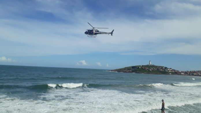 #Pracegover Foto:na imagem há um helicóptero,o mar e uma pessoa na faixa de areia