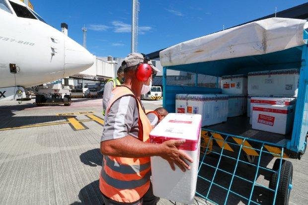 #Pracegover Foto: na imagem há uma aeronave, um homem e algumas caixas de isopor