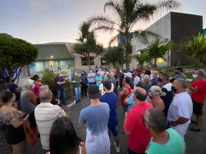 #Pracegover Foto: na imagem há inumeras pessoas, construções e palmeira