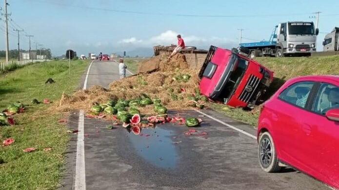#Pracegover Na foto, um caminhão tombado às margens da BR 101 e frutas espalhadas pela via.