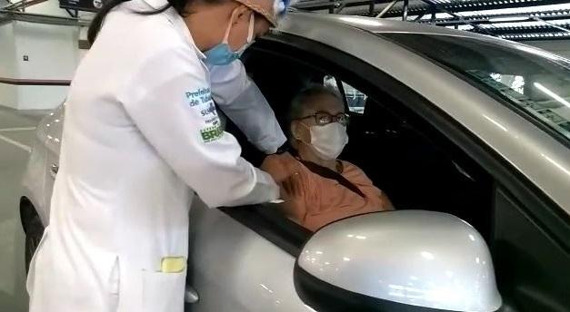 #pracegover Na foto, Carmem está sentada no banco do carro e uma enfermeira aplica a vacina